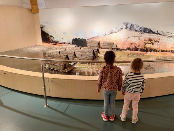 bambine che guardano plastico di villaggio palafitte