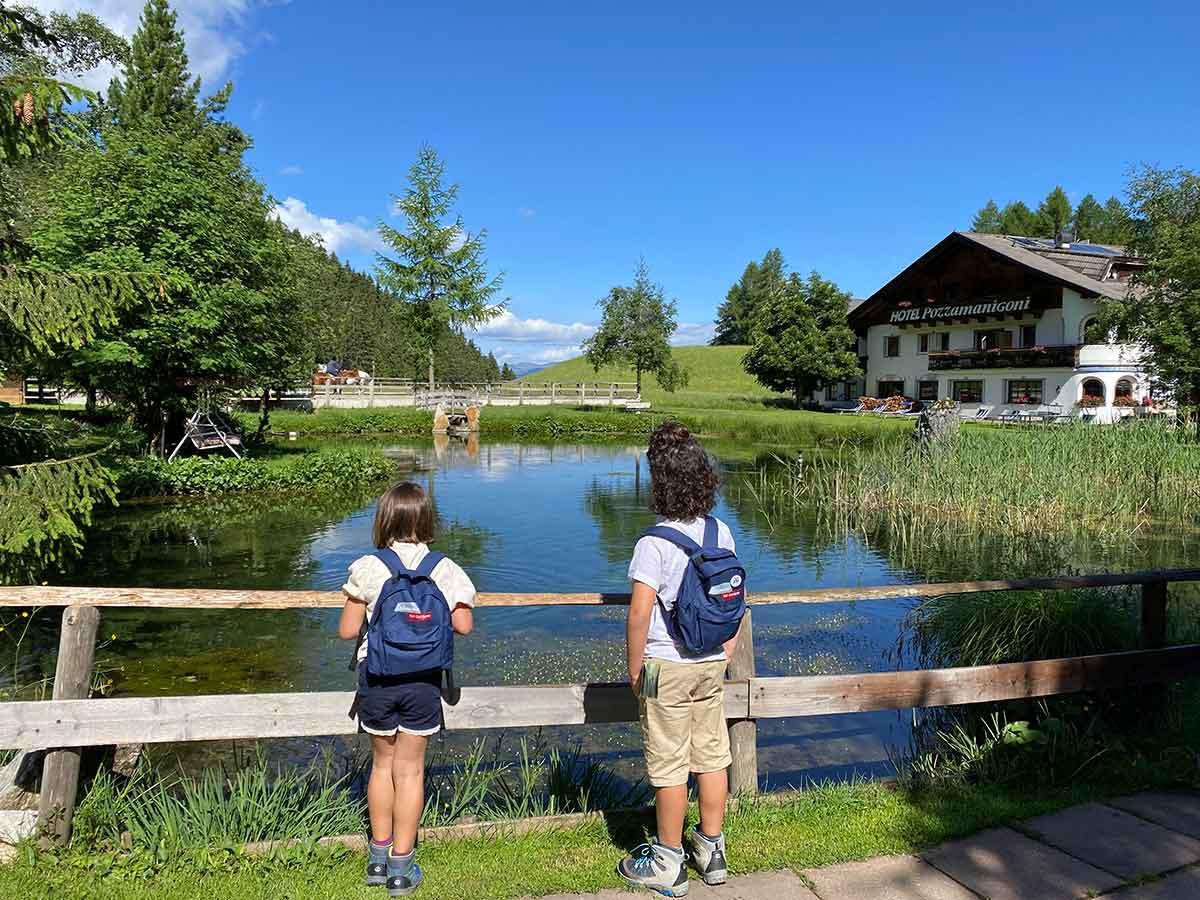 bambini di spalle davanti a un laghetto