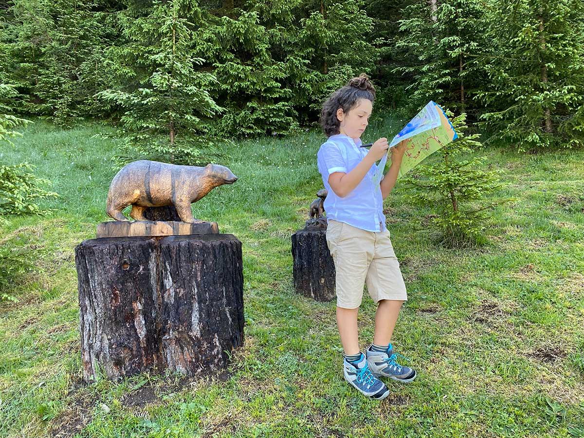 bambino con mappa e tasso scolpito nel legno