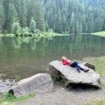 bambina sdraiata su sasso in riva al lago